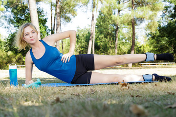 girl in blue sportswear doing exercises outdoors