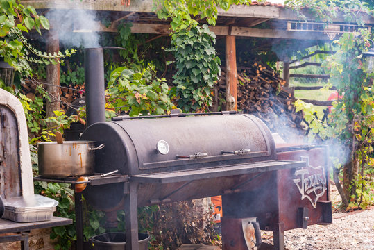 Texas Charcoal offset smoker during backyard cookout