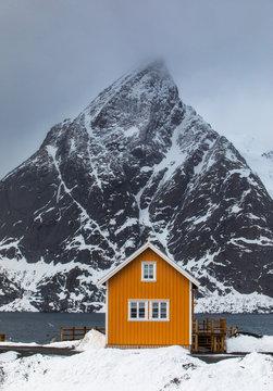 Yellow traditional rorbu house in Sakrisoy fishing village in winter on Lofoten Islands, Norway.