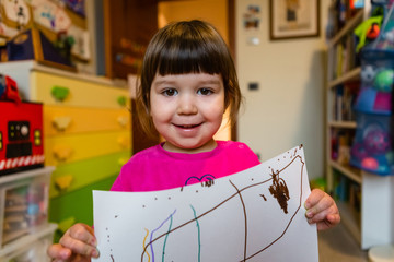Proud Toddler Girl Showing her First Drawings