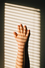 Boy's hand playing with sunlight on wall