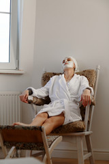 Woman with mask relaxing in armchair