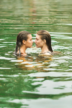 Two young women swimming in the river together.