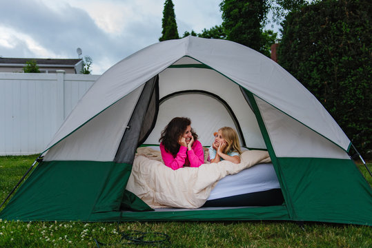 Child and adult in tent in backyard