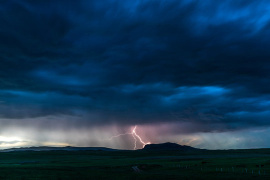 Dark cloudy sky with lightning bolt in the middle hitting the ground