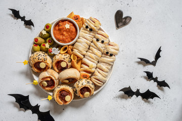 Halloween sausage mummies in dough with funny eyes on table.