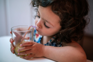 Adorable little girl drinking an orange juice
