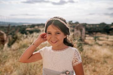 Little girl in communion dress in rustic landscape of Spain