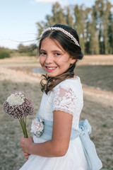 Little girl in communion dress with a bouquet of natural flowers in rustic setting