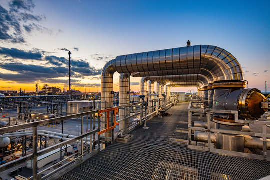 Dusk is viewed through pipe in refinery