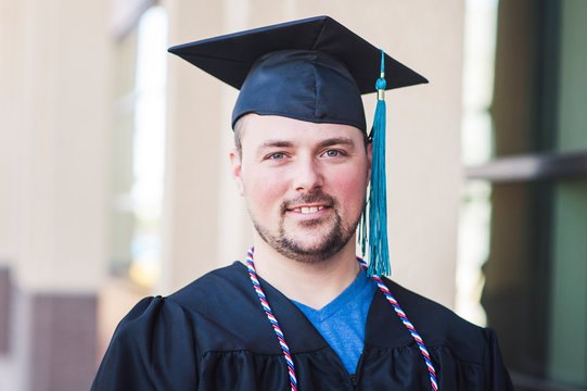 Smiling portrait of male graduate in black cap and gown
