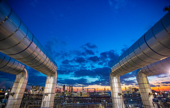 Sunset as viewed through pipe in refinery