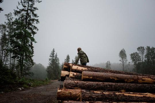 Boy climbing a pile of logs outdoors in the rain nd fog