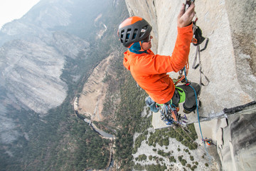 A climber ascends a rope high up on el Capitan