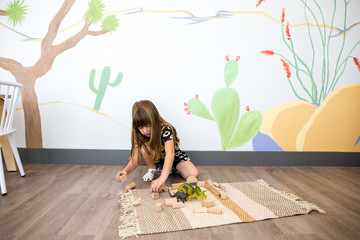 Little girl plays on the ground with blocks and dinosaurs