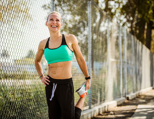 Middle aged woman smiling as she stretches to run outside