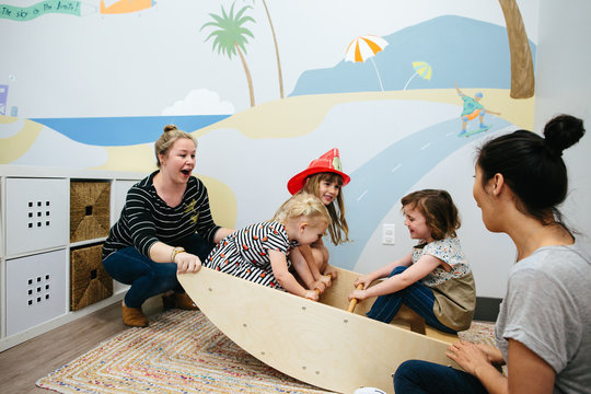Teachers rock three little girls in seesaw in the classroom