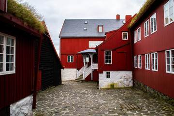 Traditional red historic wooden houses with grass (turf) roof in capital town of Faroe Islands - Tórshavn , Streymoy Island.
