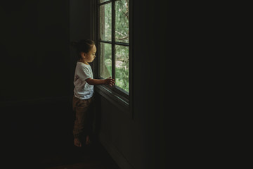 Preschool aged boy looking out the window at the trees