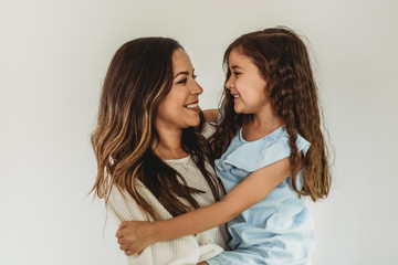 Mother and daughter looking at each other and smiling in studio