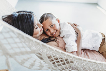 Mother and young son cuddling while laying in hammock in studio
