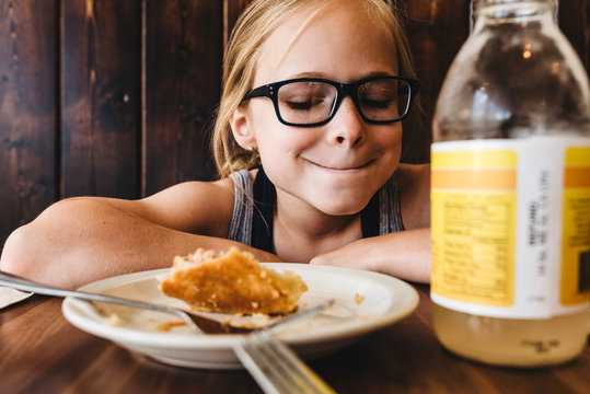 Little girl eats and drinks at table in cafe restaurant