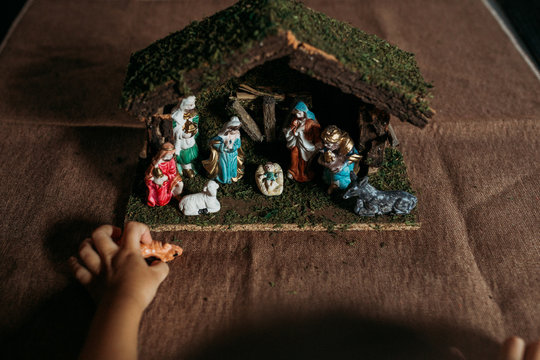 Boy playing with a nativity scene