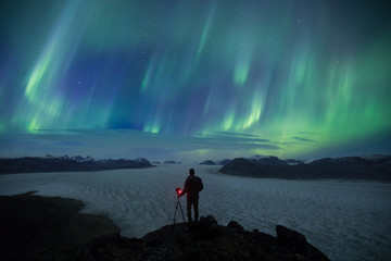 Person with a camera overlooking glacier at night under the aurora borealis