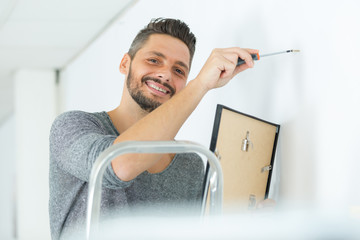 young man hanging a picture on the wall