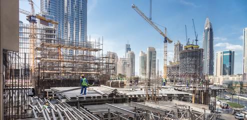 Obraz Laborers working on modern constraction site works in Dubai. Fast urban development consept. - fototapety do salonu