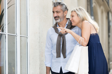 mature couple looking at fashion store window