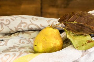Coing avec ses feuilles entier jaune à peau duveteuse après une récolte automnale posé sur un torchon gris avec des arabesques fond en bois espace négatif pour texte