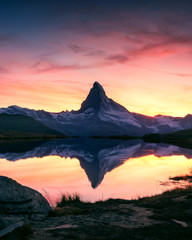 Fotobehang Alpen Splendid landscape with colorful sunrise on Stellisee lake with Matterhorn peak on background. Zermatt, Swiss Alps