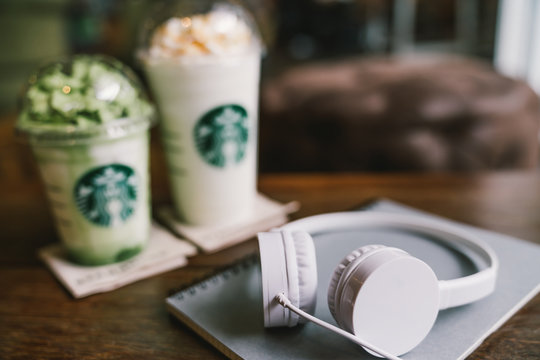 Bangkok, Thailand - Aug 30, 2018: White headphones and notebook on the table at Starbucks Coffee, with two frappucino drinks in background. Illustratative editorial