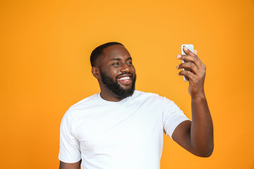 Happy African-American man taking selfie on color background