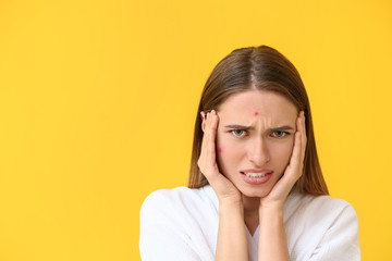 Portrait of young woman with acne problem on color background
