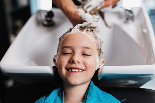 Beautiful little girl at hairsalon. Hair washing.