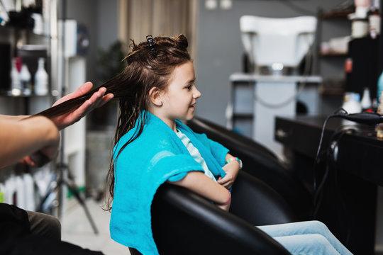 Beautiful hairstyle of cute girl in hair salon.
