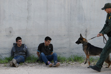 Undocumented migrants sit against a levee wall after being apprehended by U.S. Border Patrol agents near Penitas