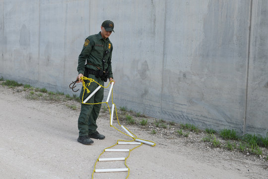 A U.S. Border Patrol agent seizes a rope ladder found rigged onto a levee wall after apprehending a group of undocumented migrants who illegally crossed the Rio Grande near Penitas