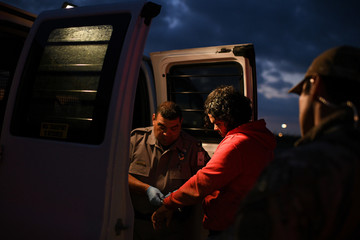 Undocumented migrants are escorted into a transport van after being apprehended by U.S. Border Patrol agents following an illegal crossing of the Rio Grande in Mission