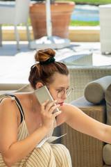 Jolie jeune femme au téléphone avec un smartphone durant son travail assise dans un patio sur un golf et appelant un client