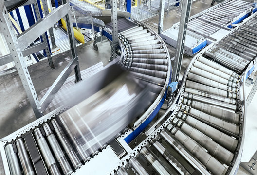 Transportation line conveyor roller with container in motion.