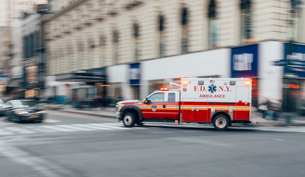 New York City, USA - March 18, 2017: FDNY Ambulance flashing lights siren blasting speed through midtown rush hour traffic in Manhattan.