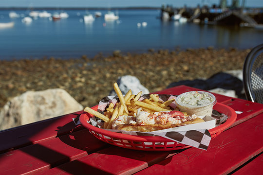 Eating traditional Maine lobster roll with coleslaw and French fries on a waterfront harbor in Maine.