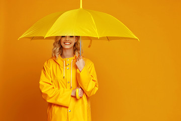 Obraz ng happy emotional girl laughing  with umbrella   on colored yellow background. - fototapety do salonu