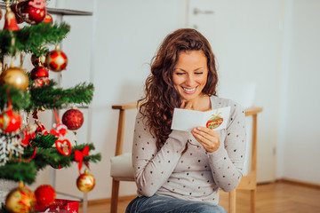 Portrait of a cute cheerful woman reading Christmas card.