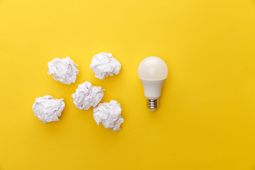 top view of light bulb near crumpled paper on yellow background