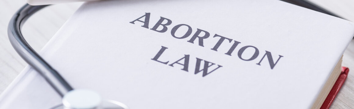 panoramic shot of book with abortion law lettering near stethoscope