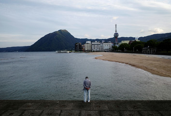A man looks on along the coast of Beppu